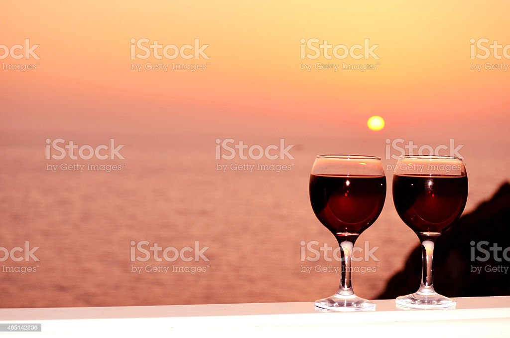 red wine glasses on a sunset background stock photo