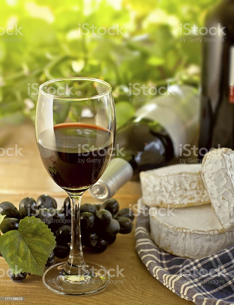 Red wine, grapes, and cheese on a wood table royalty-free stock photo
