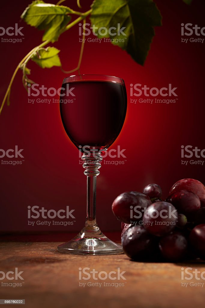 red wine in a glass and ripe grapes stock photo