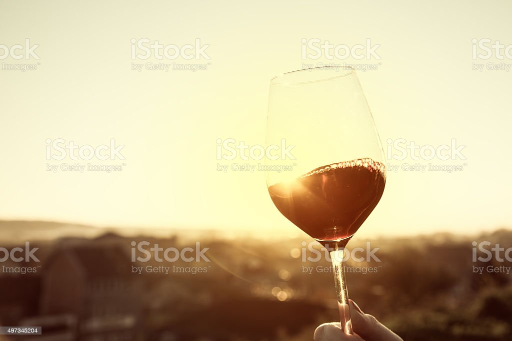 Red Wine In Crystal Glass Against Sunset stock photo