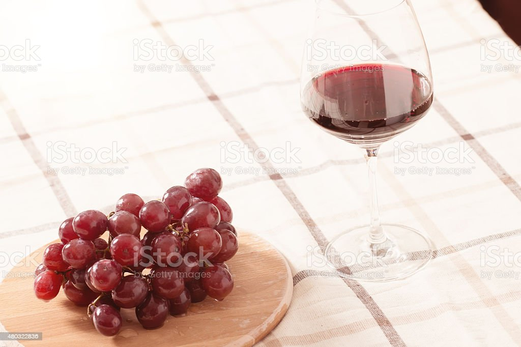Red Wine in Glass with Grapes on The Table stock photo
