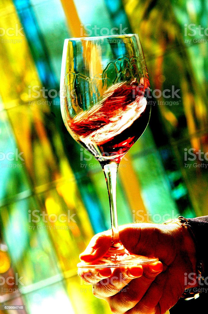 Red wine in wineglass on color background stock photo