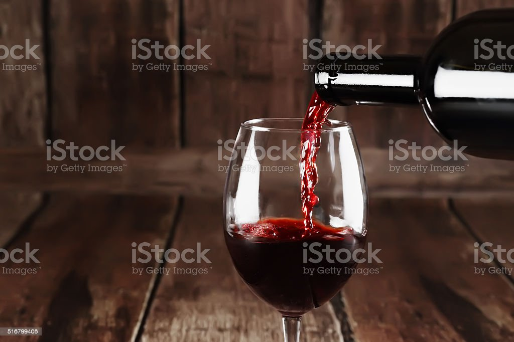 Red wine is poured from bottle to glass stock photo
