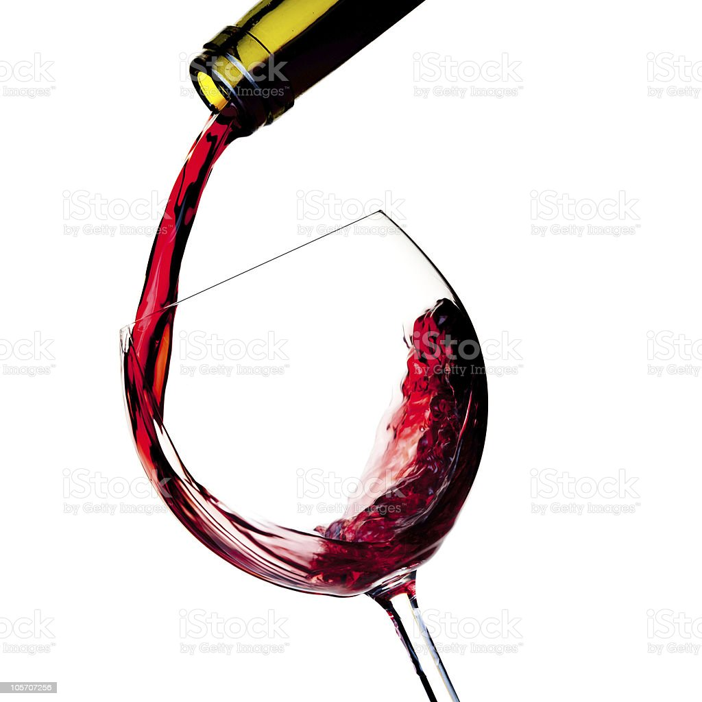 Red wine is poured into a glass from bottle stock photo