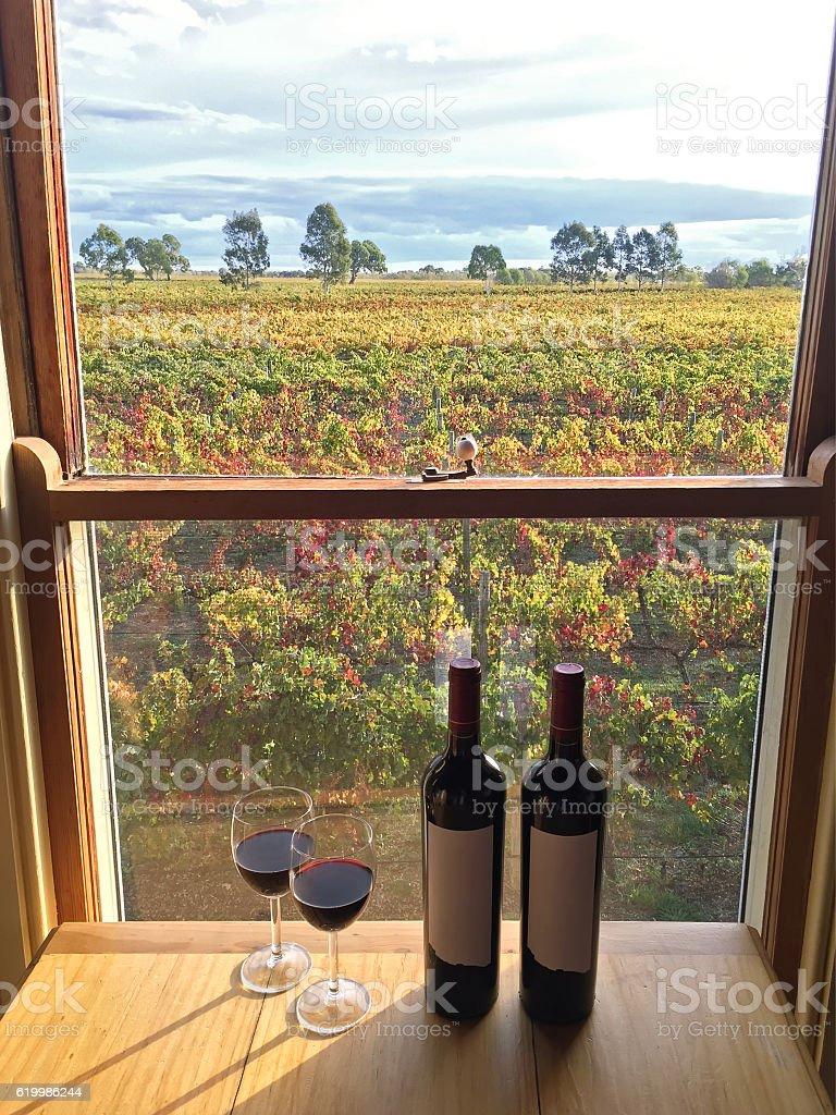 Red wine next to bottles near windows at vineyard stock photo