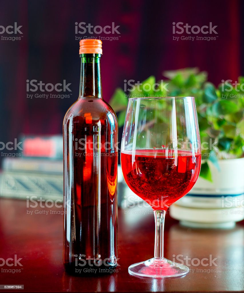 Red wine on a wooden table with books and plants stock photo