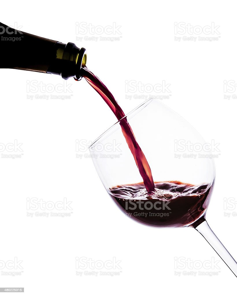 Red wine poring into wine glass. Close up. Isolated. stock photo