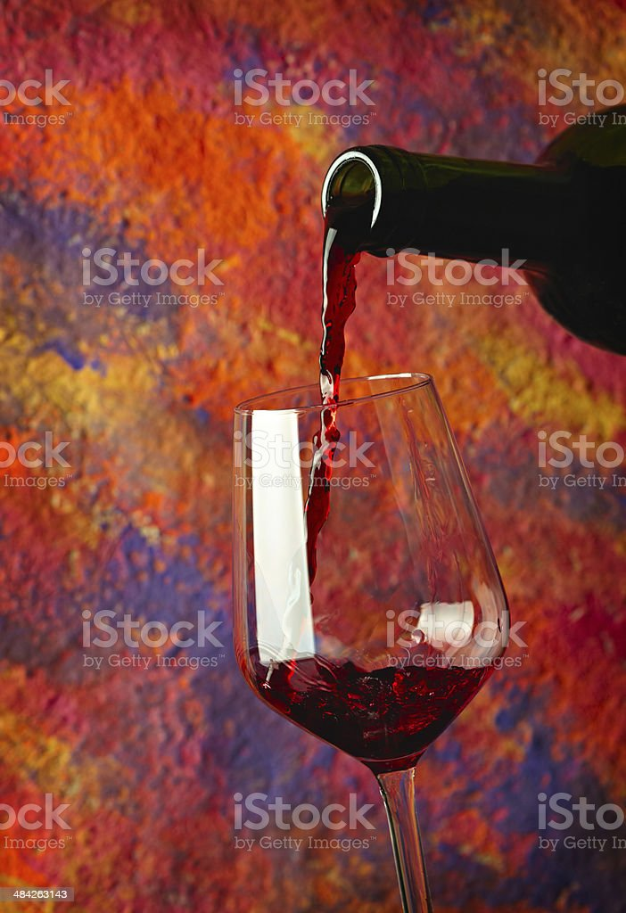 Red wine pouring in glass over grange background stock photo