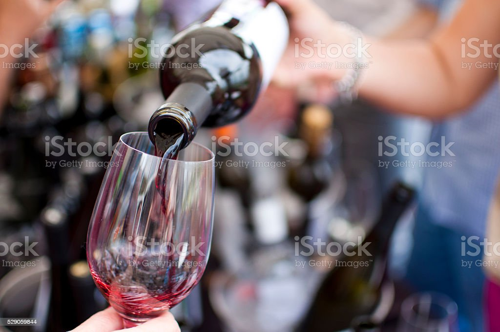 Red wine pouring in the glass stock photo