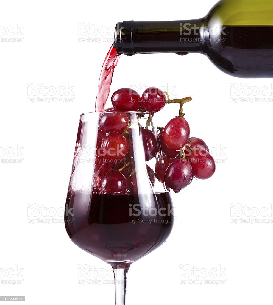 red wine pouring in the wineglass with grapes royalty-free stock photo