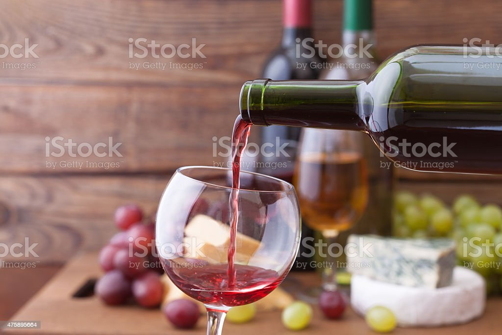 Red wine pouring into glass, close-up stock photo