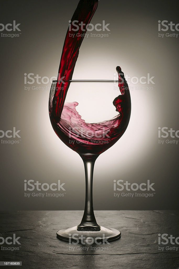 Red Wine Pouring Into Glass with Dramatic Splash royalty-free stock photo