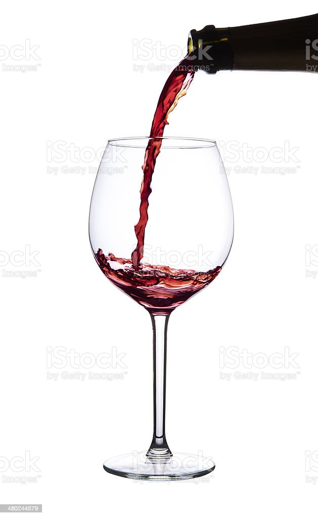Red wine pouring into wine glass. Pinot noir. Isolated. stock photo