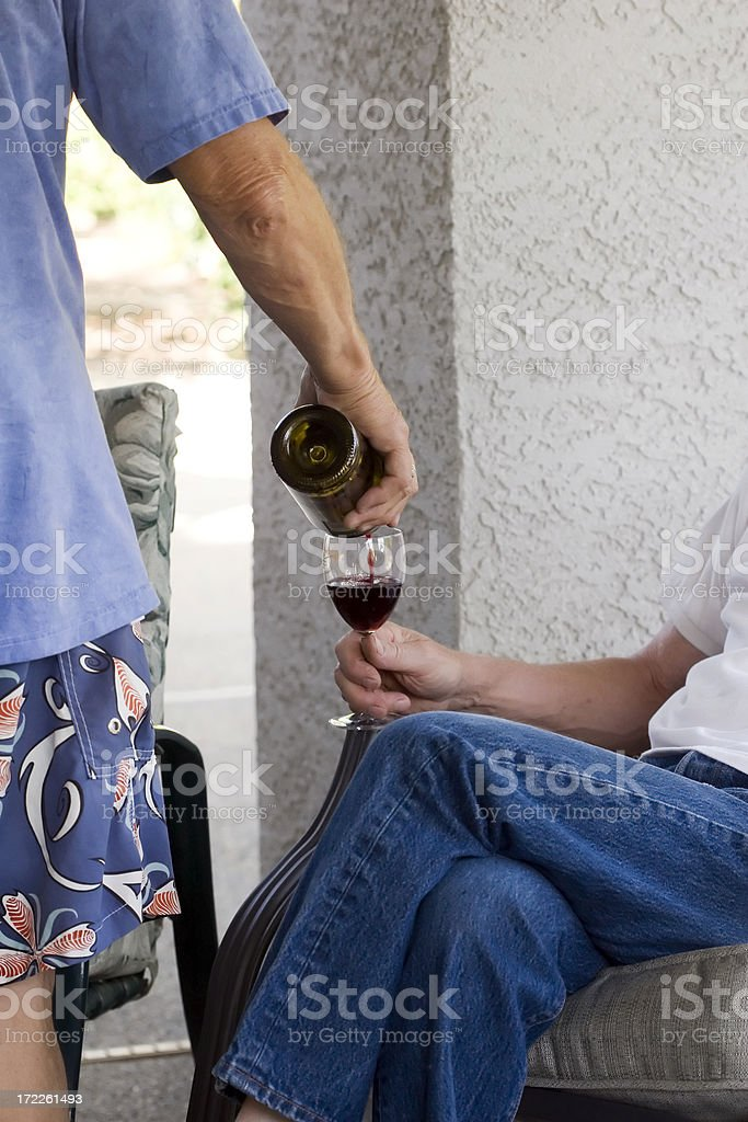 Red Wine Pouring out of Bottle into Glass stock photo