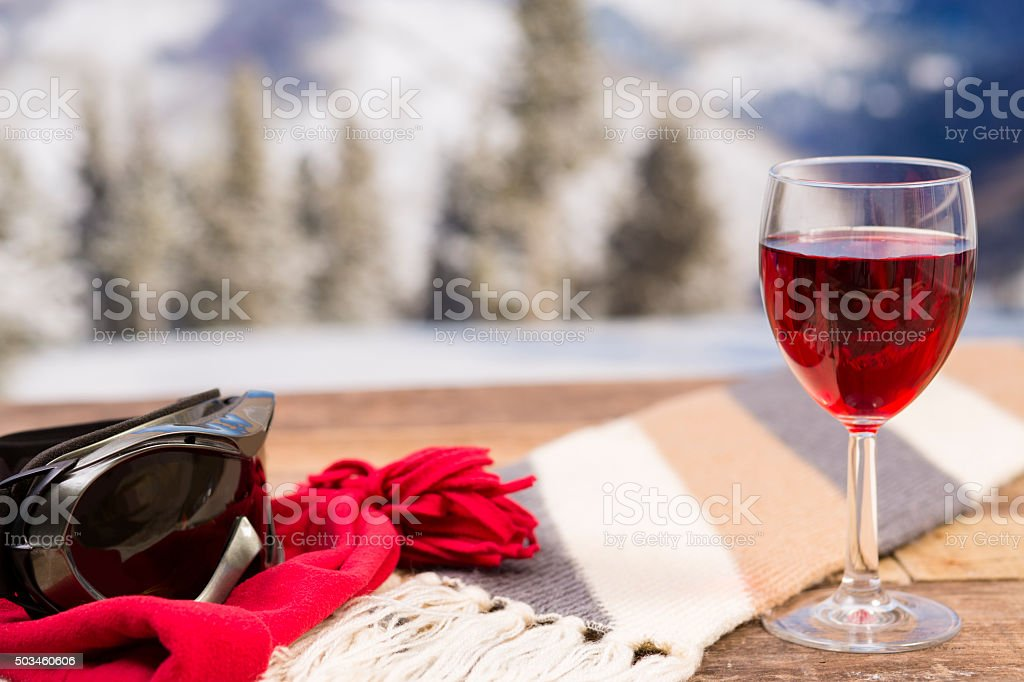 Red wine, ski goggles with winter mountains background. stock photo