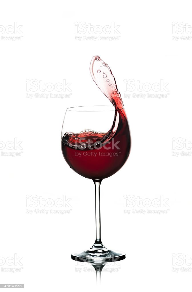 Red Wine Splashing In A Glass stock photo