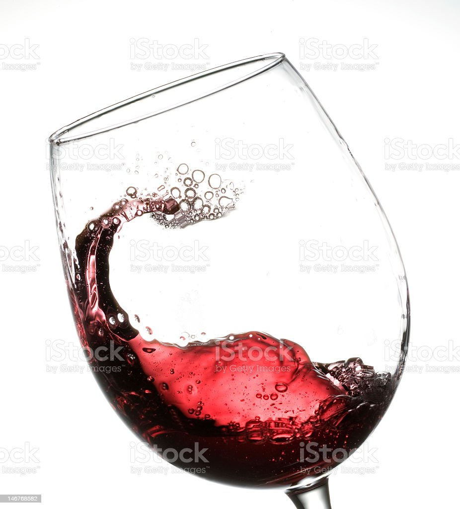 Red wine swishing in a glass on a white background royalty-free stock photo