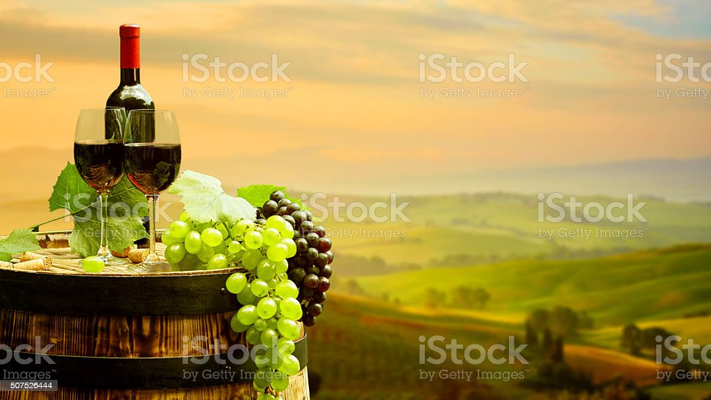Red wine with barrel on vineyard in green Tuscany stock photo