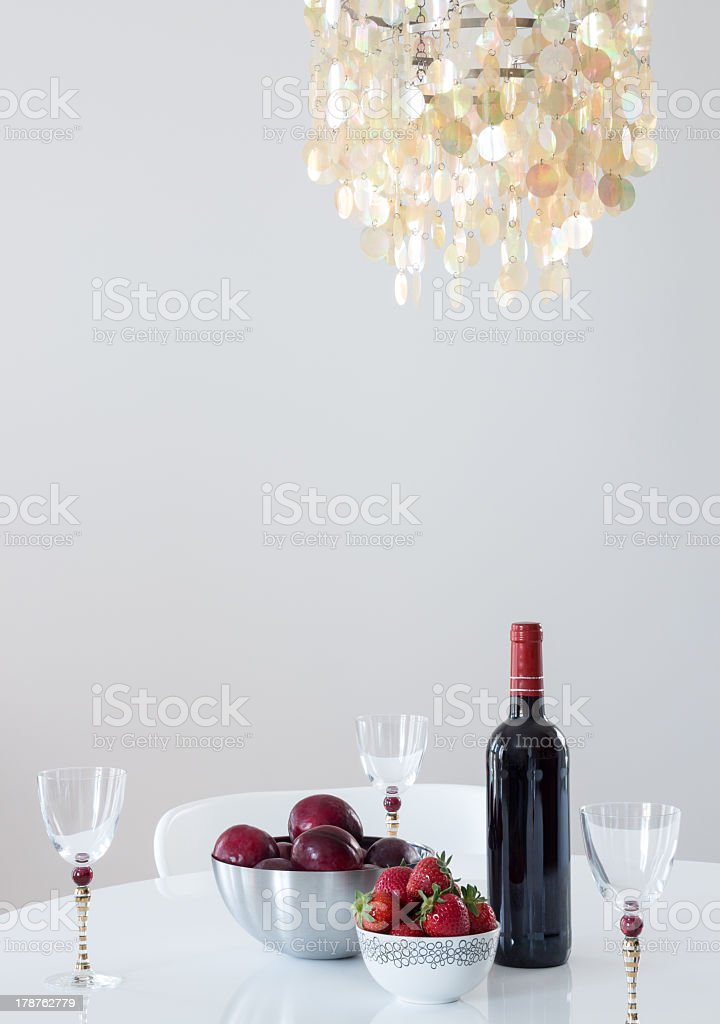 Red wine with fruits on a table, and beautiful chandelier royalty-free stock photo