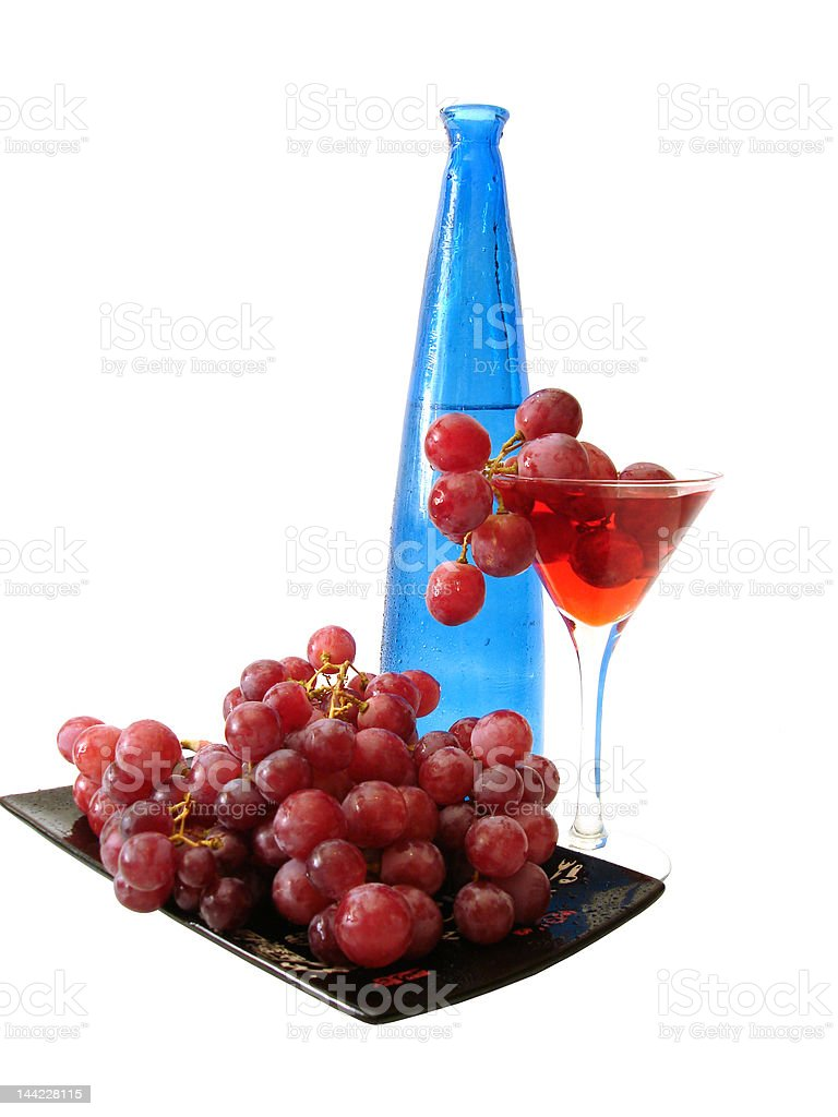 red wine with grapes and blue bottle over white background royalty-free stock photo