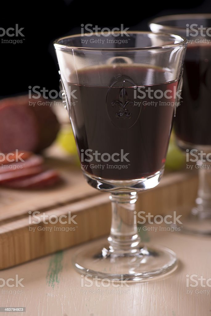 Red wine with salami grapes on old wood stock photo