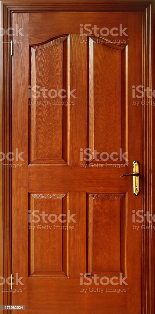 Red wood colored door with gold hinges and door knob stock photo