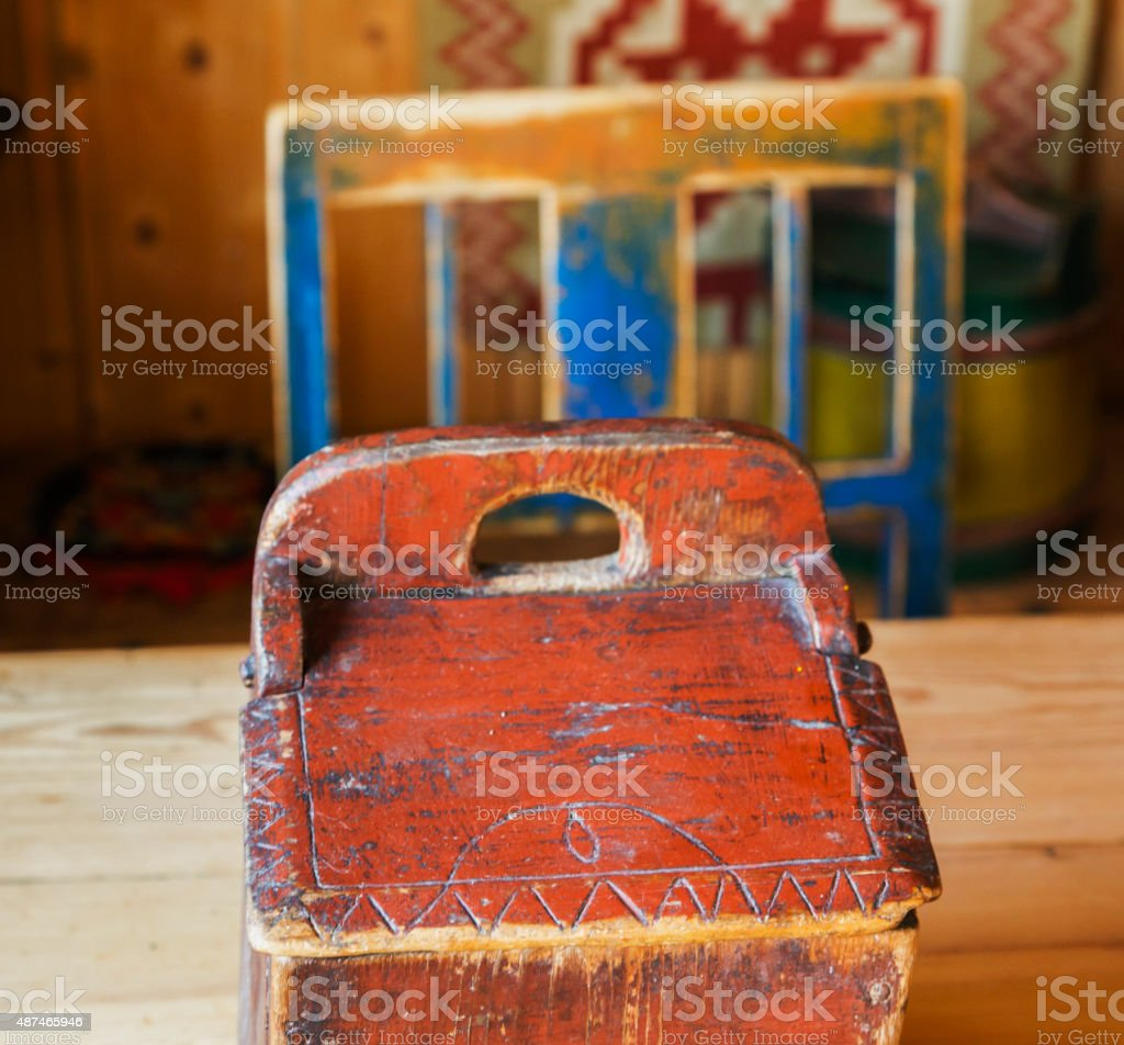 Red wooden box in front of blue painted Norwegian chair. stock photo