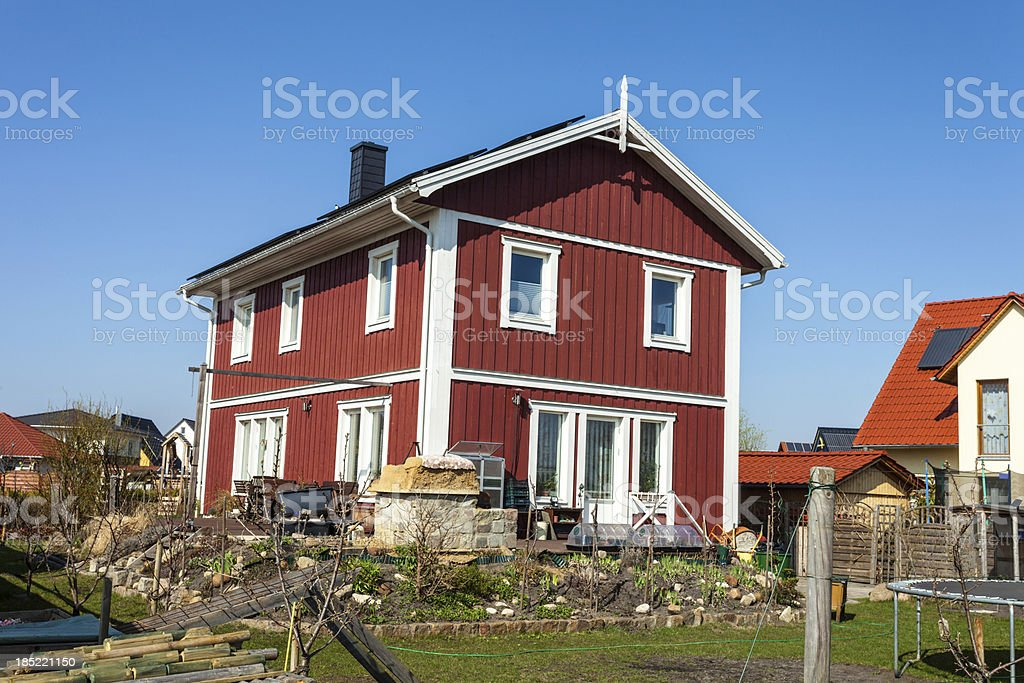 Red wooden cottage in spring stock photo