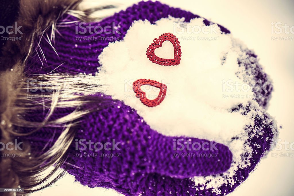 Red wooden hearst in the hands with snow stock photo