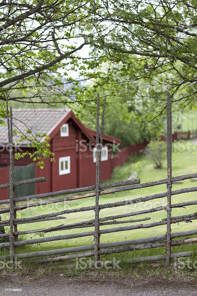 Red wooden house behind the fence stock photo