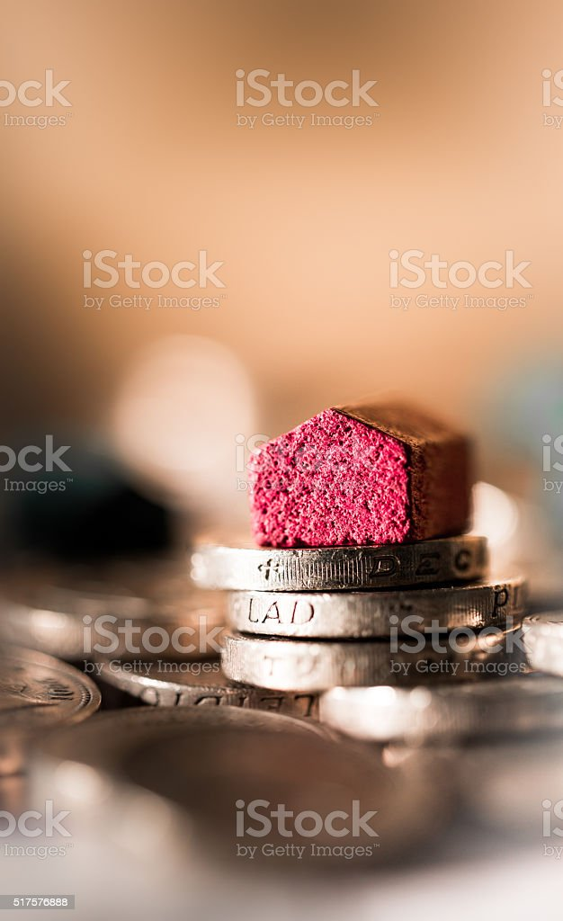 Red wooden house on top of British pound coins stock photo