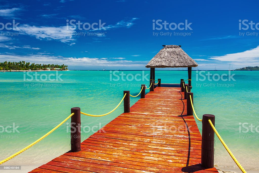 Red wooden jetty extending to tropical ocean on Fiji Island stock photo