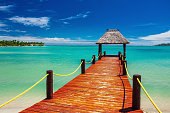 Red wooden jetty extending to tropical ocean on Fiji Island