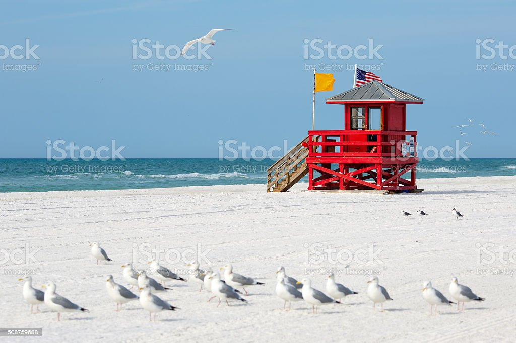 Red wooden lifeguard hut on an empty beach stock photo