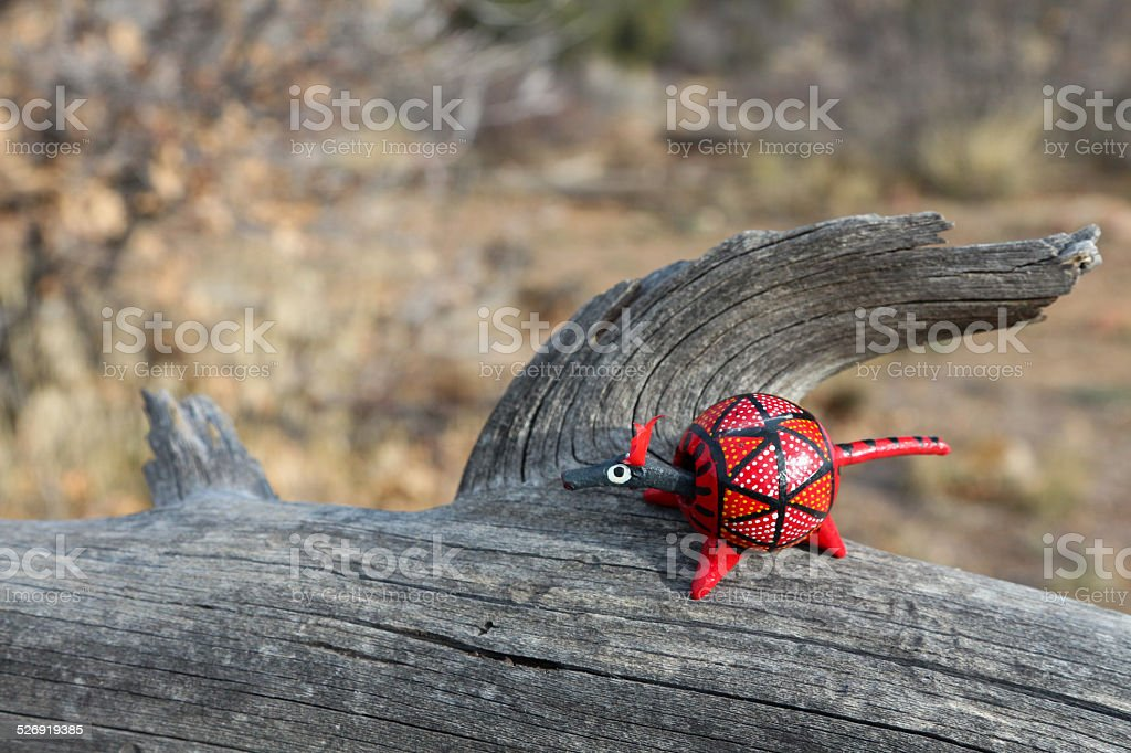 Red wooden toy armadillo on a dead tree stock photo