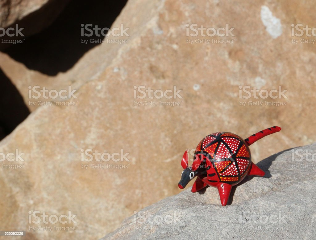 Red wooden toy armadillo on a tan rock stock photo