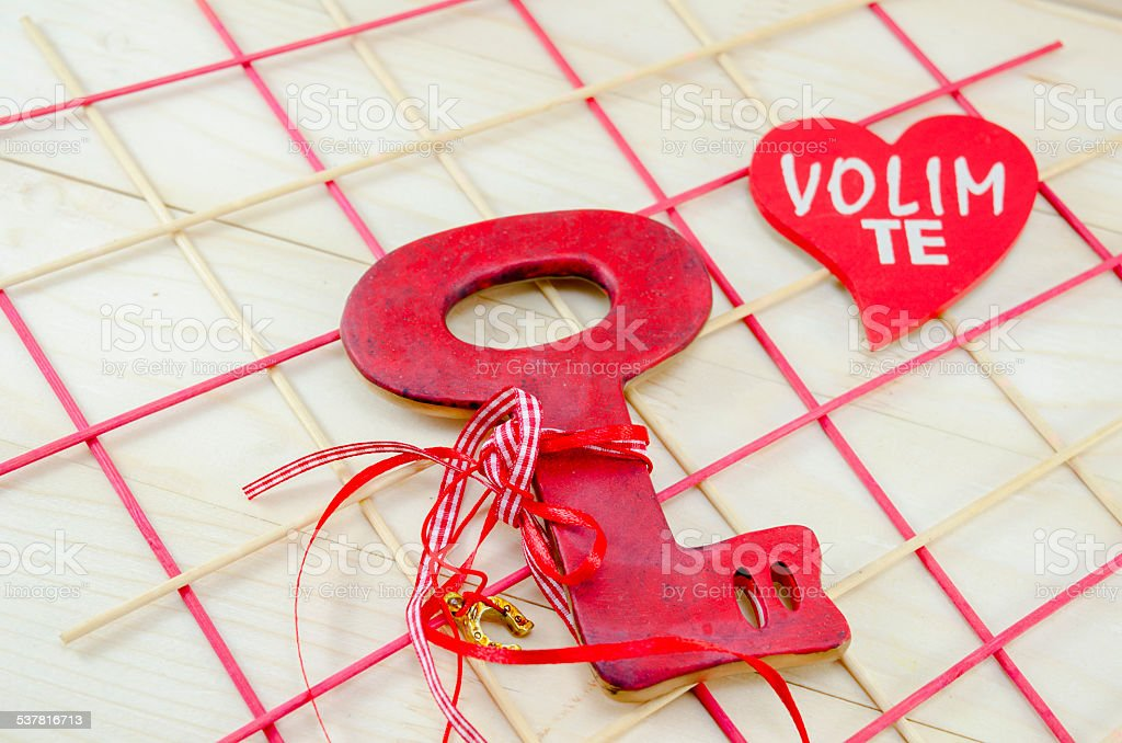 Red wooden vintage key on wooden surface royalty-free stock photo