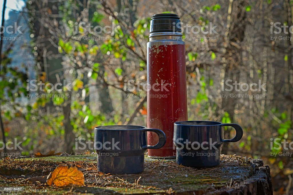 Red worn out thermos bottle with two blue cups stock photo