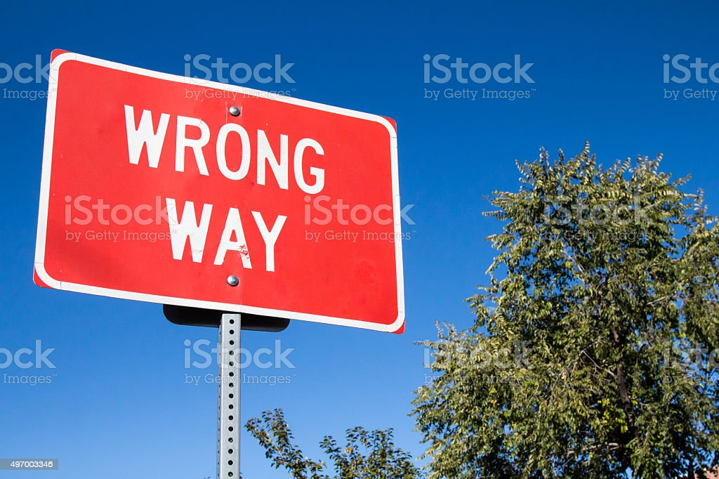 Red wrong way sign against blue sky stock photo
