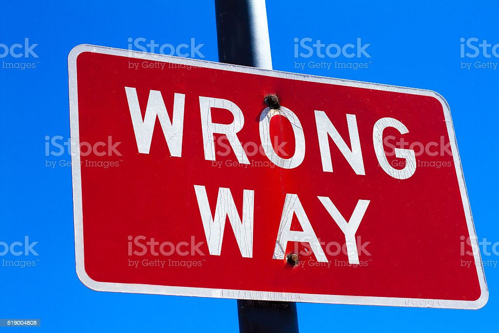 Red 'WRONG WAY' Sign Against Deep Blue Sky stock photo