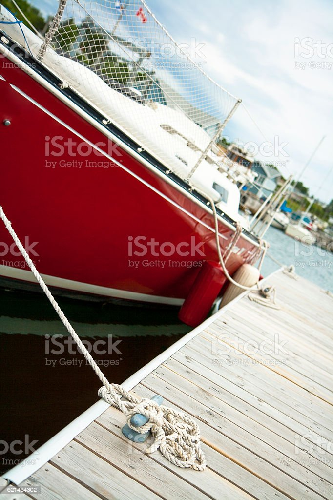 Red yacht by dock stock photo