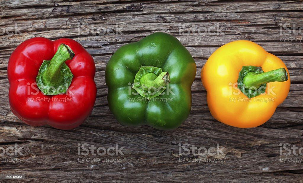 Red, yellow and green bell peppers on the wood background stock photo