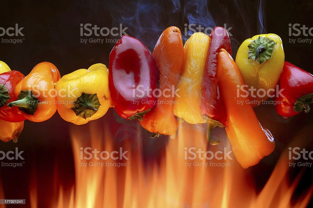 Red yellow and orange peppers over an open fire royalty-free stock photo