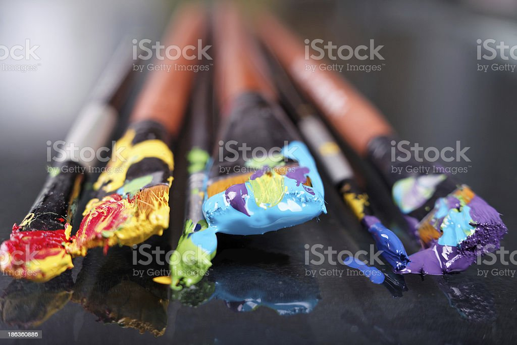 Red, yellow, green, blue and purple paint on paint brushes stock photo