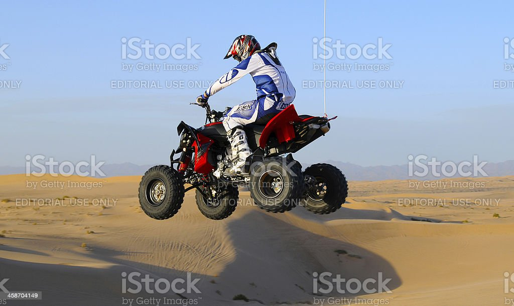 Red/black ATV Jump in Sand Dunes stock photo