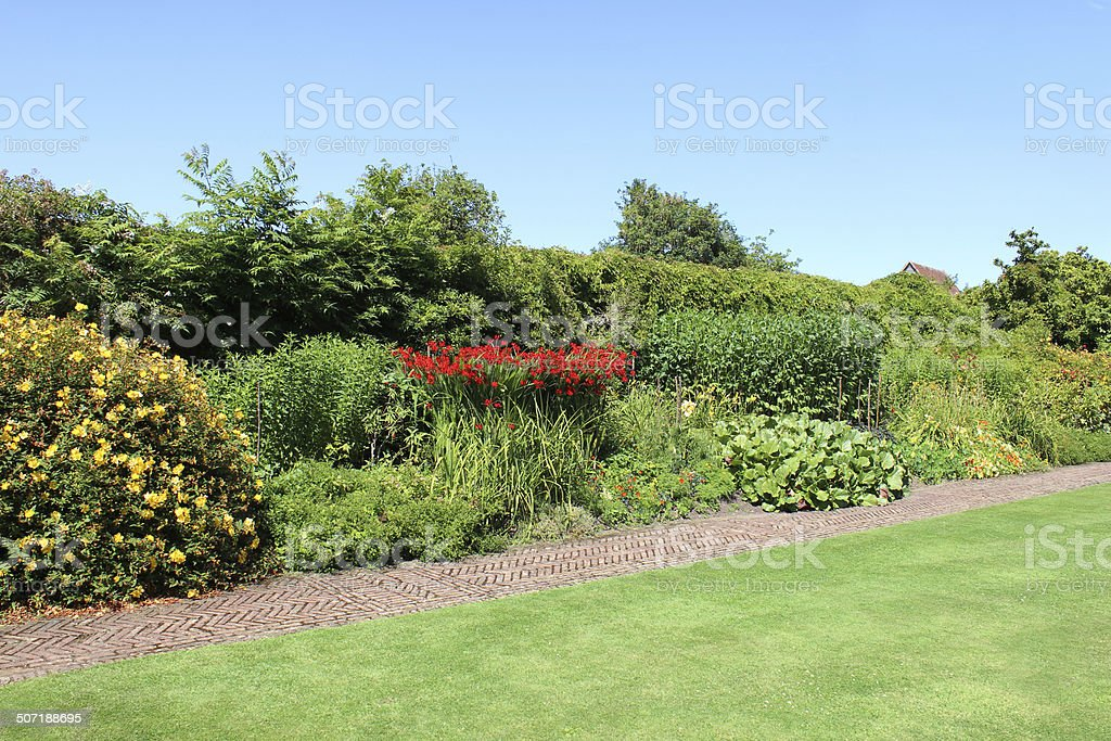 Red-brick path, block paving image, paved pathway, herbaceous-border, flowers, lawn royalty-free stock photo