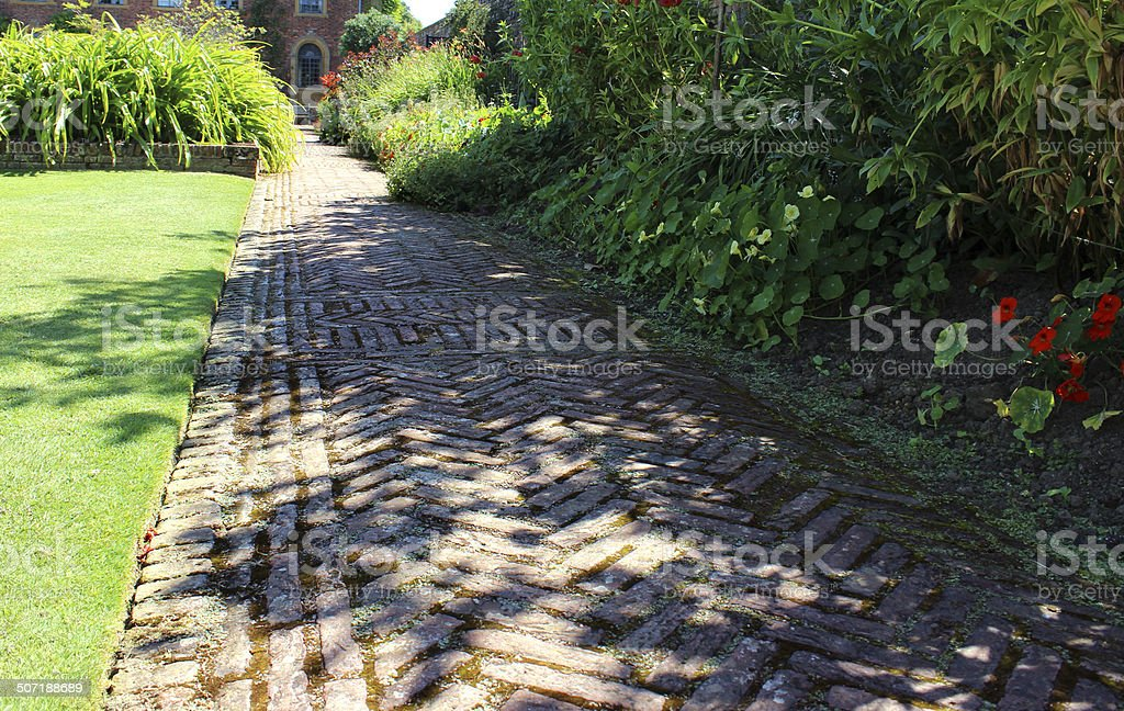 Red-brick path, block-paving image, paved pathway, herringbone-pattern, lawn, shady garden royalty-free stock photo