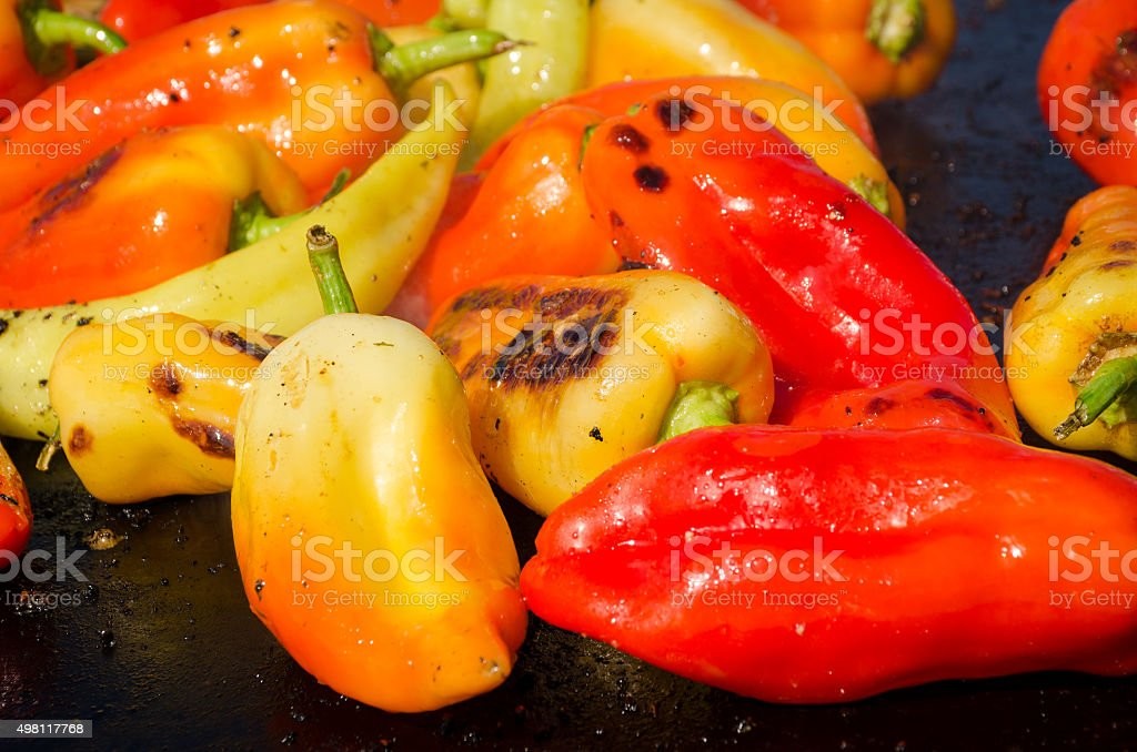 Red,green,yellow peppers on a grill stock photo