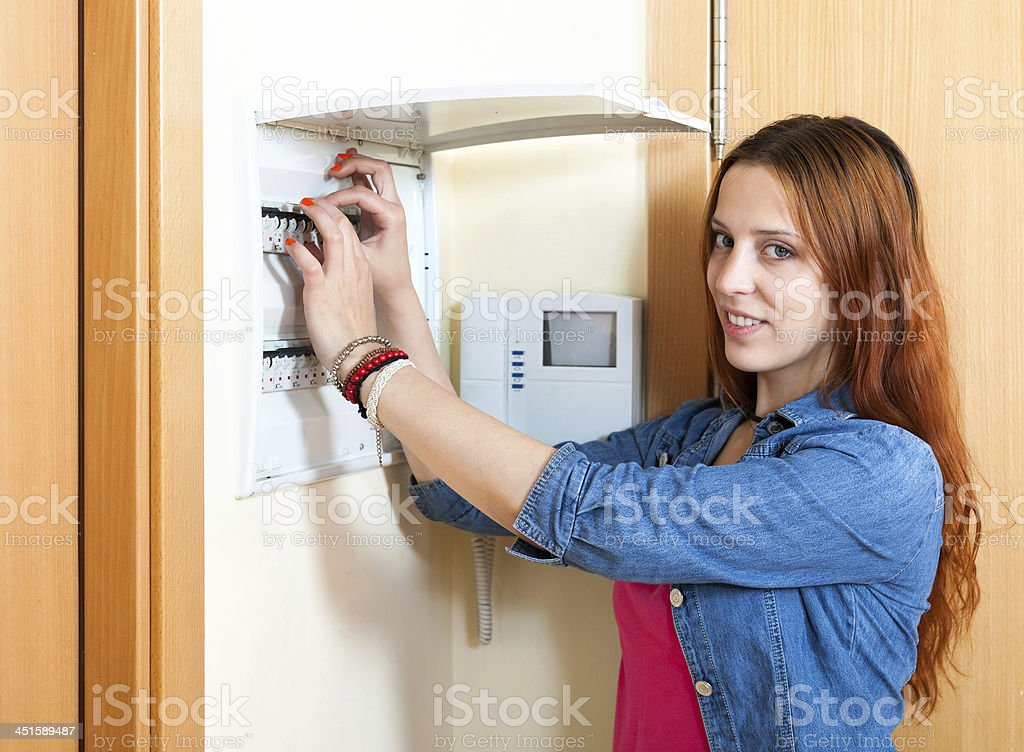 Red-haired cute woman turning off the light-switch at power cont stock photo