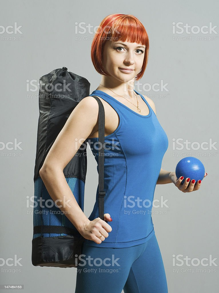 Red-haired fitness girl with yoga mat stock photo